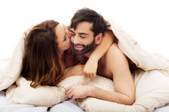 Beautiful couple under the cover in their bed. Royalty Free Stock Photo