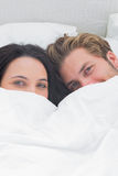 Beautiful couple under the duvet. Looking at camera Stock Photography