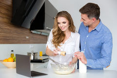 Beautiful couple using laptop and cooking together Stock Photos