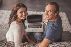 Couple at home. Beautiful couple is using a laptop, looking at camera and smiling while resting on couch at home stock photography