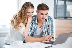Beautiful couple using laptop and working together Stock Images