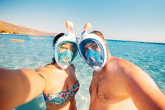 Beautiful couple in vacation, taking selfie with underwater camera, snorkeling and smiling Royalty Free Stock Photo