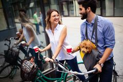 Beautiful couple walking dogs and bicycles outdoors in city stock photos