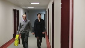 Beautiful couple walking in the hall the hospital. Young man with glasses and a beautiful girl in a black dress goes a long corridor holding hands stock footage