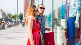 Beautiful couple walking through the mall carrying a lot of shopping bags. Royalty Free Stock Photo
