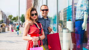 Beautiful couple walking through the mall carrying a lot of shopping bags. In the background window dressing Royalty Free Stock Photo