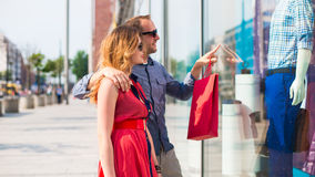 Beautiful couple walking through the mall carrying a lot of shopping bags. He is showing window dressing Royalty Free Stock Photography