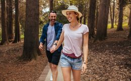 Beautiful couple walking through park and smiling. Beautiful women in casuals wearing hat walking with her men holding hand at the autumn park. Beautiful couple royalty free stock images