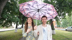 Beautiful couple walking under umbrella in park stock footage