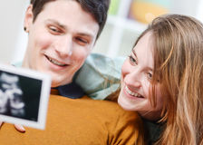 Beautiful couple watching with emotion ultrasound pictures Stock Photo