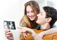 Beautiful couple watching with emotion ultrasound pictures of their baby Royalty Free Stock Photography