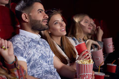Beautiful couple watching interesting film at cinema and smiling. Stock Images