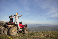 Beautiful couple is watching the sunset from the mountain sitting on quadbike.  Stock Photography