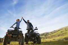 Beautiful couple is watching the sunset from the mountain sitting on quadbike.  Royalty Free Stock Photo