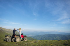Beautiful couple is watching the sunset from the mountain sitting on quadbike.  Stock Image