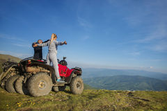 Beautiful couple is watching the sunset from the mountain sitting on quadbike.  Royalty Free Stock Photos