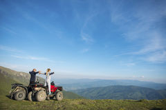 Beautiful couple is watching the sunset from the mountain sitting on quadbike.  Royalty Free Stock Images