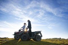 Beautiful couple is watching the sunset from the mountain sitting on quadbike.  Stock Photo