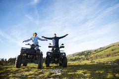Beautiful couple is watching the sunset from the mountain sitting on quadbike.  Royalty Free Stock Photography