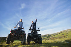 Beautiful couple is watching the sunset from the mountain sitting on quadbike.  Stock Photos