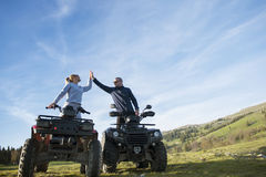 Beautiful couple is watching the sunset from the mountain sitting on quadbike.  Stock Images