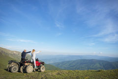 Beautiful couple is watching the sunset from the mountain sitting on quadbike.  Royalty Free Stock Image