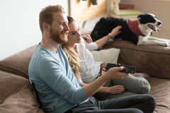 Beautiful couple watching television at home with their dog Stock Image
