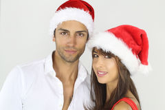 Beautiful couple wearing a Santa hat. Over a white background Stock Image