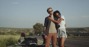 A beautiful couple wearing sunglasses are sitting by the road near their motorbike and are staring straight into the stock video footage
