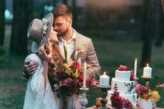 beautiful couple on wedding standing near cake stock images
