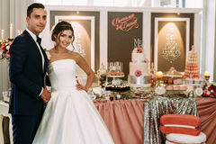 Beautiful couple and wedding table with sweets Stock Photos