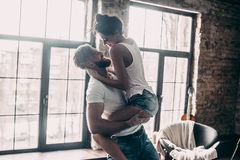 Beautiful couple. Young passionate couple having fun together and looking happy while handsome young men carrying his girlfriend in hands Royalty Free Stock Photo
