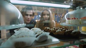Beautiful couple of young people in a candy store. The girl and the guy chosen Cake and desserts for themselves stock video