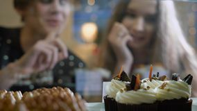Beautiful couple of young people in a candy store. A girl and a guy in a sweater choose Cake and desserts for themselves stock video
