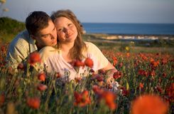 Beautiful couple young women and young man in flowers Royalty Free Stock Photo