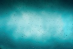 Beautiful cover of gradient background. Rain drops on glass with dark clouds. Greeting for design. Beautiful cover of blue gradient background. Rain drops on Stock Photo