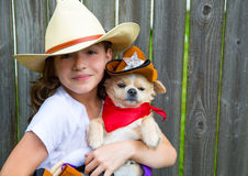 Beautiful cowboy kid girl holding chihuahua with sheriff hat. Beautiful cowboy kid girl holding chihuahua dog with sheriff hat in backyard wooden fence stock photography