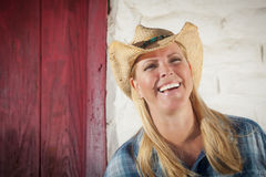 Beautiful Cowgirl Against Old Wall and Red Door Royalty Free Stock Photography