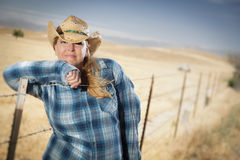 Beautiful Cowgirl Against Wire Fence in Field Royalty Free Stock Image