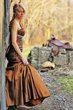 Beautiful cowgirl in a formal dress near a cement wall royalty free stock photo