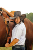 Beautiful cowgirl with her horse. Beautiful cowgirl with her bay horse Royalty Free Stock Photos