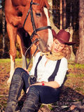 Beautiful  cowgirl with her red horse Royalty Free Stock Photo