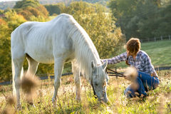 Beautiful cowgirl with her white horse Stock Image