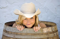 Beautiful cowgirl peek out of a barrel looking sly. A beautiful young cowgirl peeks out of a barrel, looking like she has a secret stock photography