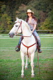 Beautiful cowgirl riding a white horse Royalty Free Stock Photo