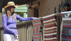 A Beautiful Cowgirl Shops for Indian Blankets. A Beautiful Brunette Cowgirl Shops for Handmade Native American Blankets Stock Photo