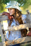 Beautiful cowgirl in stetson. Portrait of beautiful cowgirl in stetson next to wooden fence Royalty Free Stock Photos