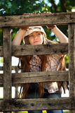 Beautiful cowgirl in stetson. Looking through fence Royalty Free Stock Photography