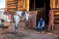 Beautiful Cowgirl in Western Scene. A beautiful cowgirl petting her horse at the barn door. Very western royalty free stock image