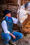 Beautiful Cowgirl in Western Scene. A beautiful cowgirl petting her horse at the barn door. Very western stock photo